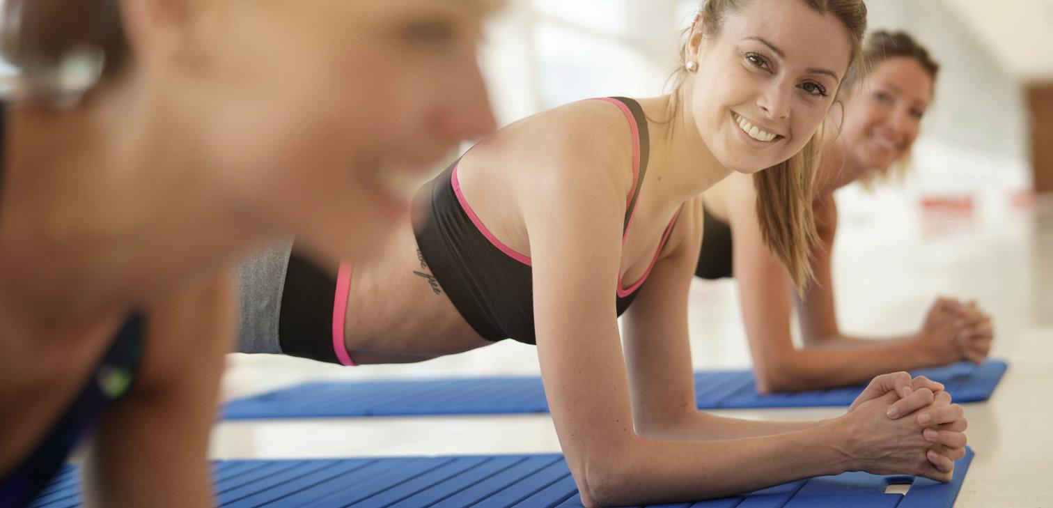 Drei Frauen machen eine Plank in einem Fitness Kursraum