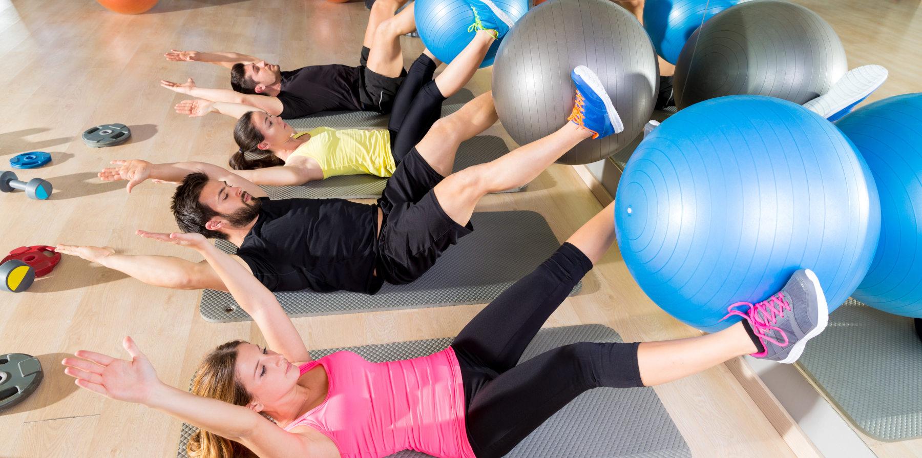Gruppe macht Fitness im Kursraum und liegt auf dem Ruecken und hebt eine Gymnastikball mit ihren Fuessen waehrend einer Bauchuebung hoch