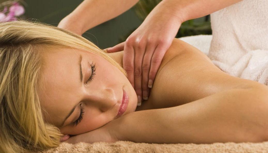 Eine Frau mit entspanntem Gesichtsausdruck liegt auf einer liege, zwei Hände massiere ihre Schultern